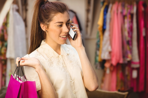 Vrouw die op mobiele telefoon spreekt terwijl het winkelen