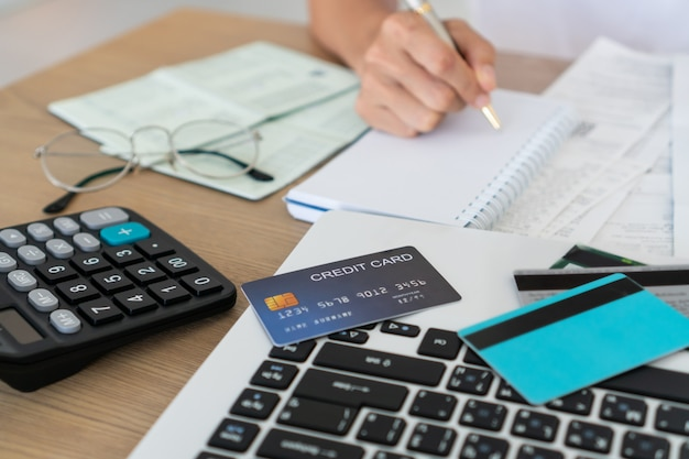 Vrouw die op notitieboekje met computer, calculator en creditcard op bureau, rekening en besparingsconcept schrijven.