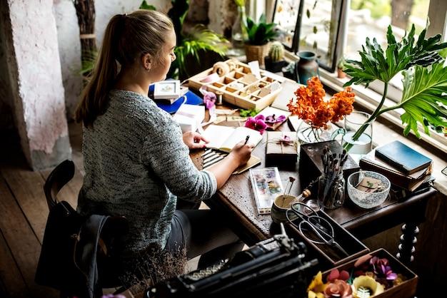 Vrouw die op notitieboekje op werkruimte verfraaide wih bloem schrijft