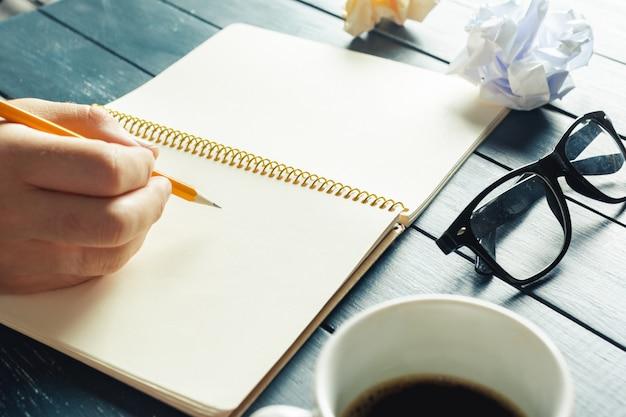 Vrouw die op notitieboekje schrijft