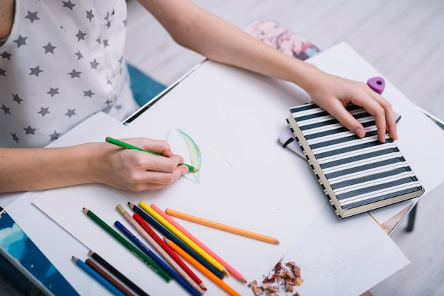Vrouw die op papier bij lijst met reeks van potloden en notitieboekje schildert