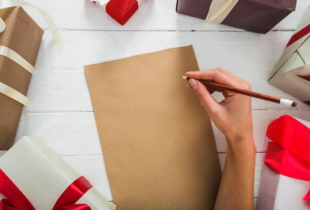 Vrouw die op papier met potlood schrijft