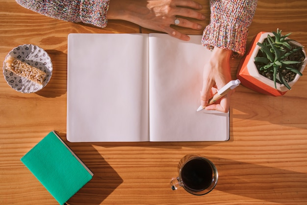Vrouw die op pen met leeg wit notitieboekje over het houten bureau schrijft