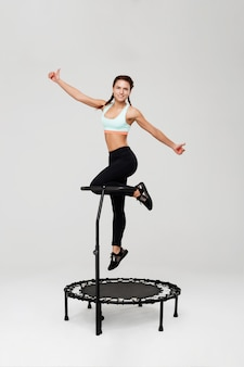 Vrouw die op rebounder omhoog tonend duimen met glimlach springen