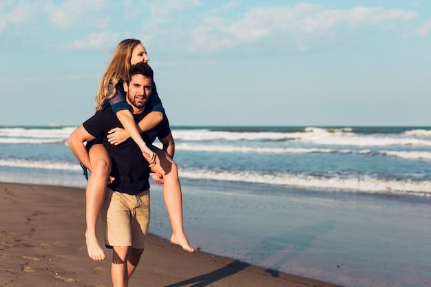 Vrouw die op rug van de mens op strand berijden