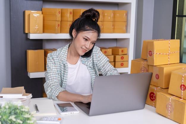Vrouw die op smartphone en gebruikcomputerlaptop spreekt aan het verkopen van product online van huisbureau