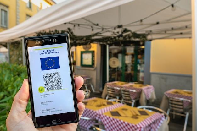 Vrouw die op smartphone eu digitaal covid-certificaat groene pas laat zien