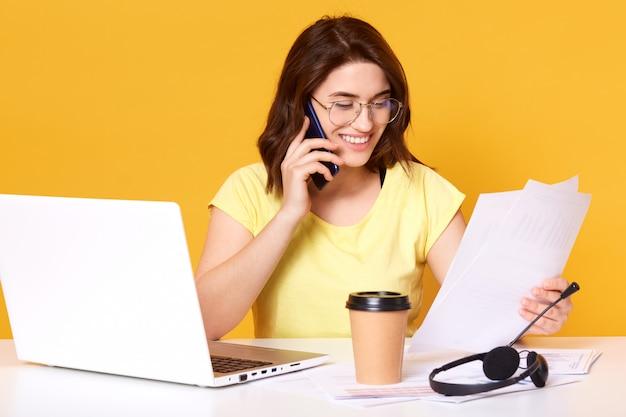 Vrouw die op smartphone spreekt en documenten houdt. de dame roept mobiele telefoon op, werkt in bureau, spreekt met cliënt die op geel wordt geïsoleerd. communicatie- en adviesconcept.