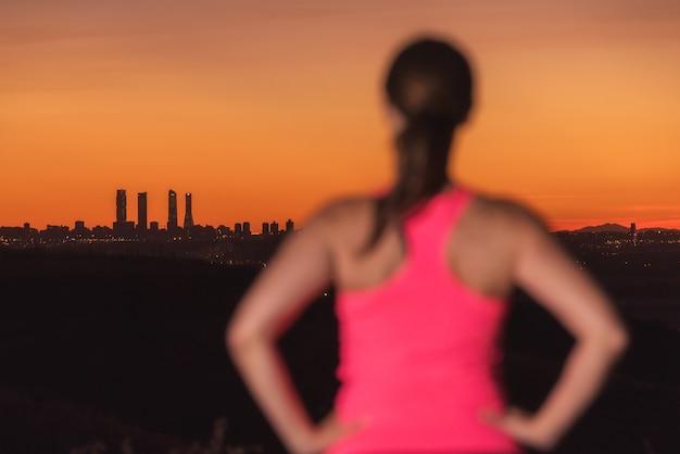 Vrouw die op sportkleren op zonsondergang over stadshorizon letten. focus ligt op de achtergrond.