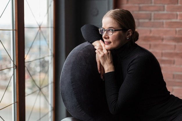 Vrouw die op stoel weg kijkt
