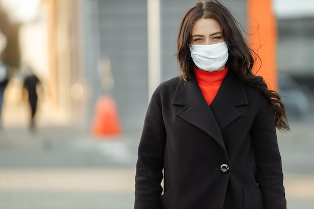Vrouw die op straat loopt die beschermend masker draagt
