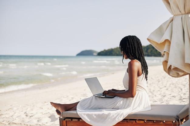Vrouw die op strand met laptop rust