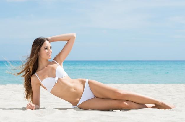 Vrouw die op strand zonnebaadt
