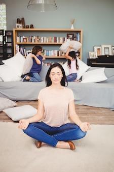 Vrouw die op tapijt mediteren terwijl kinderen het spelen