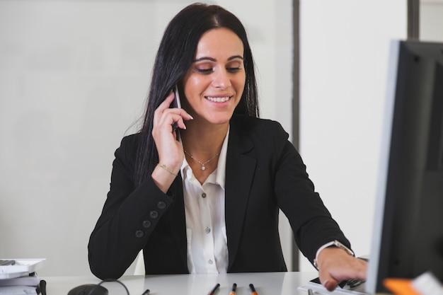 Vrouw die op telefoon bij computer spreekt