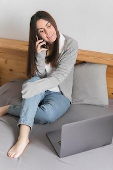 Vrouw die op telefoon dichtbij laptop in bed spreekt