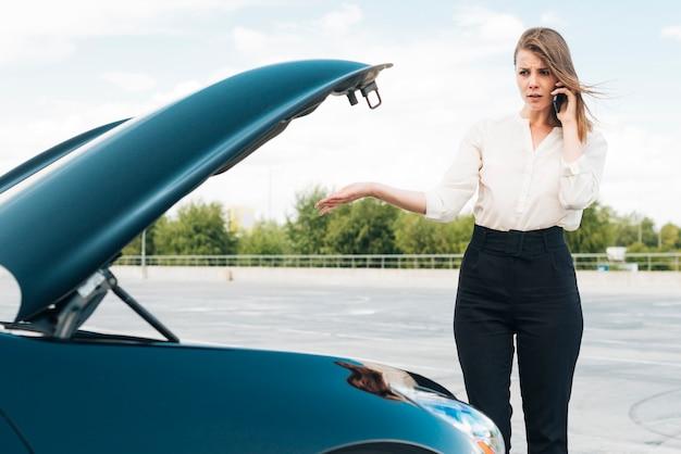 Vrouw die op telefoon en auto spreekt