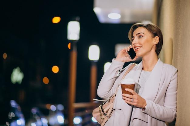 Vrouw die op telefoon en het drinken koffie buiten in de straat bij nacht spreken