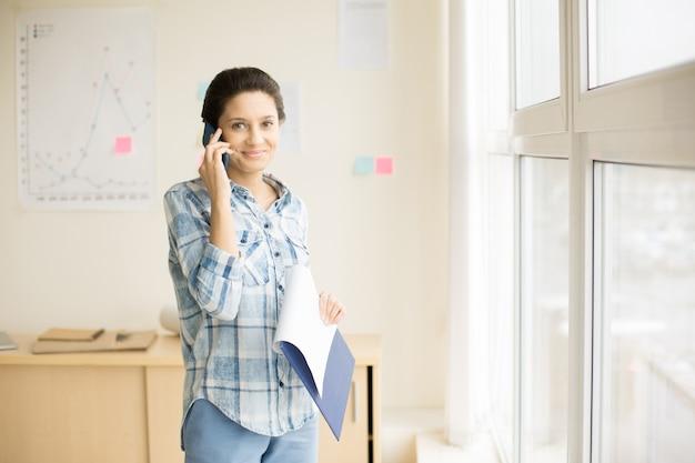 Vrouw die op telefoon in bureau spreekt