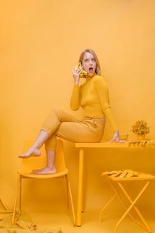 Vrouw die op telefoon in een gele scène spreekt