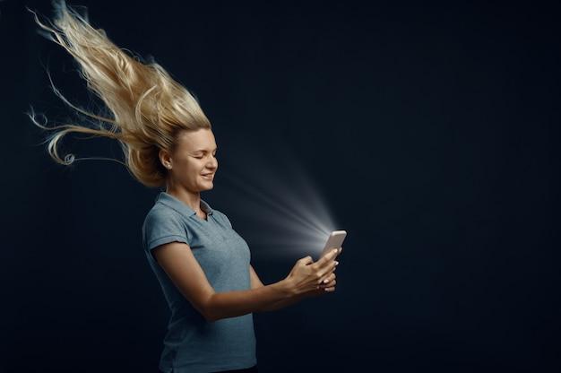 Vrouw die op telefoon kijkt tegen krachtige luchtstroom in studio, achteraanzicht, kapseleffect ontwikkelen. vrouwelijke persoon en wind, dame geïsoleerd op donkere achtergrond