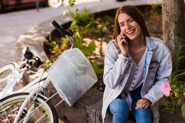 Vrouw die op telefoon naast fiets spreekt
