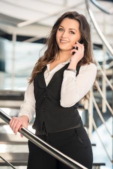 Vrouw die op telefoon op treden in een modern bureau spreekt.