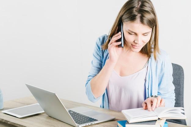 Vrouw die op telefoon spreekt en notitieboekje controleert