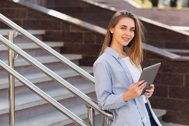 Vrouw die op traliewerk rust en een tablet houdt