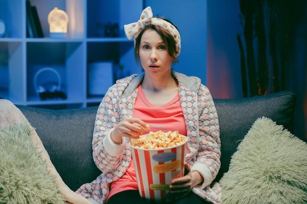 Vrouw die op tv lacht en popcorn eet die pret heeft alleen thuis genietend van moderne televisie.