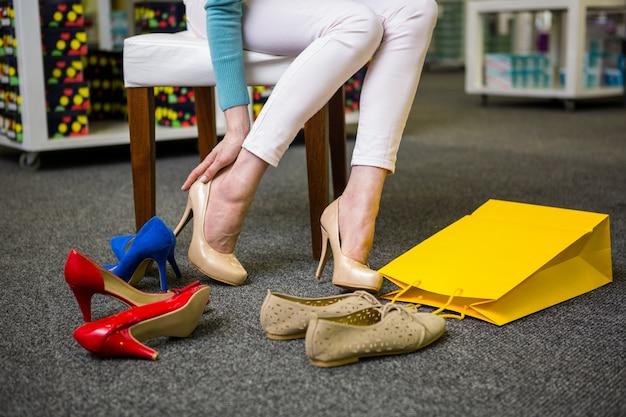Vrouw die op verschillende schoenen probeert