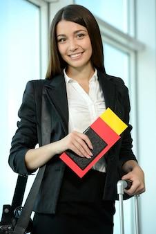 Vrouw die op vliegtuigtickets op uw vlucht op luchthaven wacht.