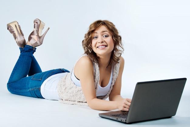 Vrouw die op vloer met laptop het glimlachen ligt