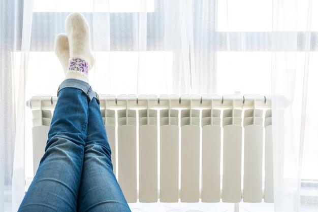 Vrouw die op vloer met voeten legt die op radiator voor het opwarmen worden opgeheven