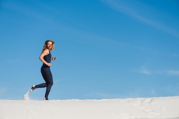 Vrouw die op zand in sportslijtage loopt