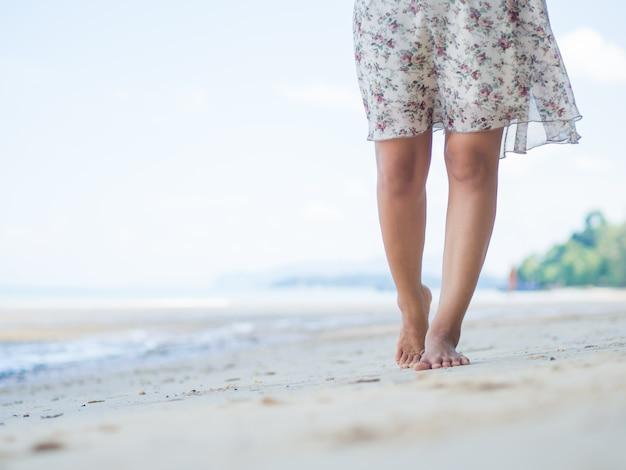 Vrouw die op zandstrand loopt. close-updetail van vrouwelijke voeten