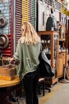 Vrouw die op zoek is naar iets om te kopen op een antiekmarkt