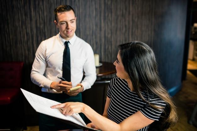 Vrouw die opdracht geeft aan kelner van het menu in een restaurant