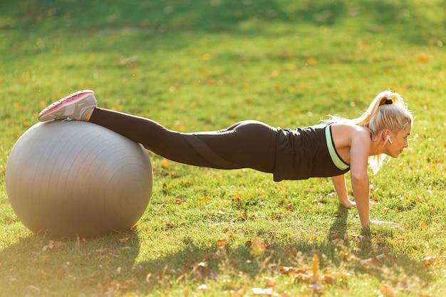 Vrouw die opdrukoefeningen doet die gymnastiekbal gebruiken