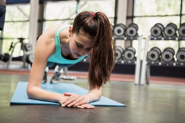 Vrouw die opdrukoefeningen in gymnastiek doet