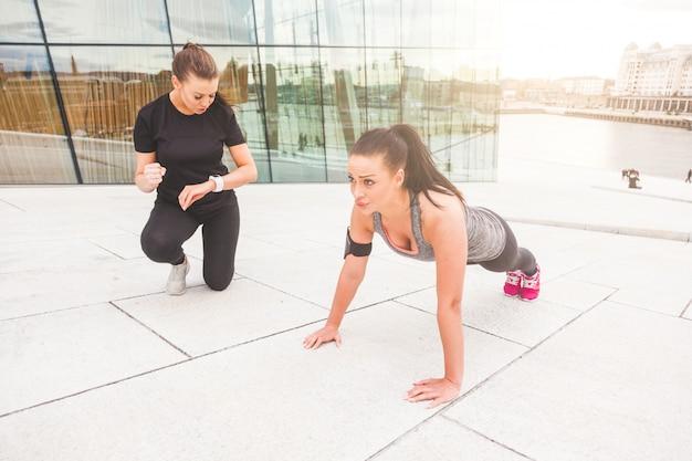 Vrouw die opdrukoefeningenoefeningen met haar persoonlijke trainer doet