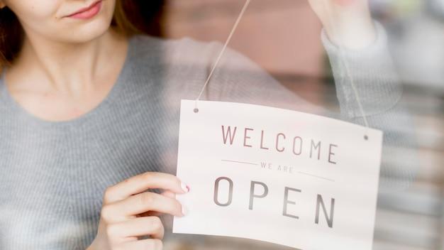 Vrouw die open teken op venster voor koffiewinkel hangt