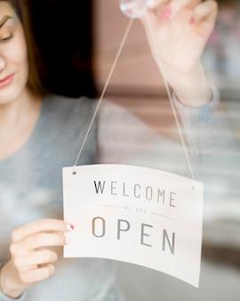 Vrouw die open teken op venster voor koffiewinkel zet