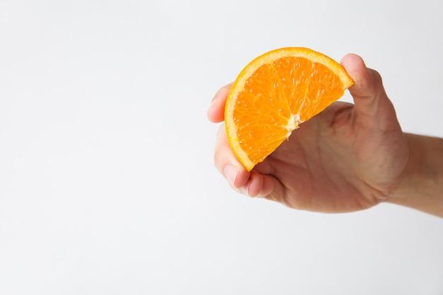 Vrouw die oranje plak voor sap houdt