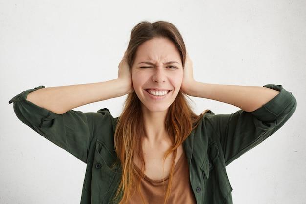 Vrouw die oren dichtstopt met vingers die haar ogen sluiten die geen lawaai willen luisteren