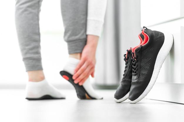 Vrouw die orthopedische inlegzolen past. behandeling en preventie van platte voeten en voetziekten. voetverzorging, voetcomfort. gezondheidszorg. sport comfortabele schoenen dragen