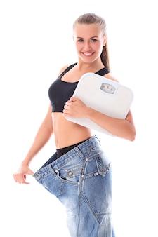 Vrouw die oude jeans na gewichtsverlies draagt