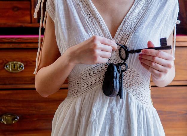 Vrouw die oude sleutel houdt en in handen vergrendelt