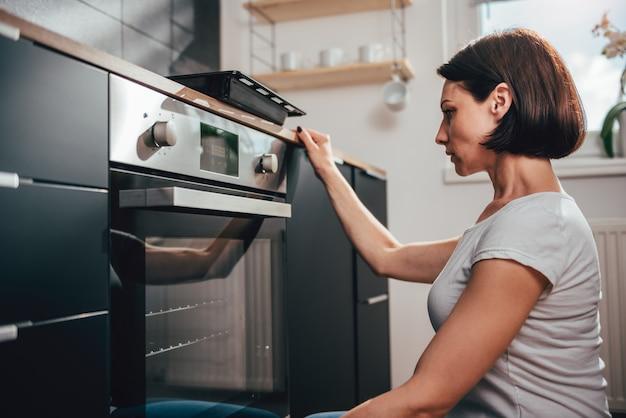 Vrouw die oven gebruikt