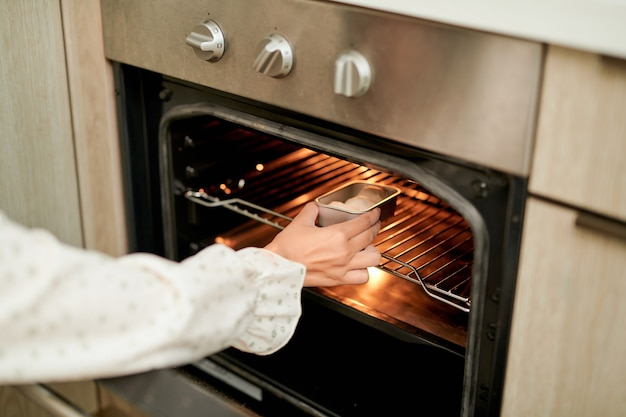 Vrouw die ovenwant draagt die bakplaat met ruwe koekjes in moderne oven in huiskeuken zet